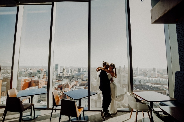 Bride and groom embracing in front of a high rise building window