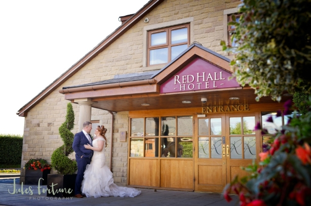Bride and groom standing outside of the Red Hall Hotel