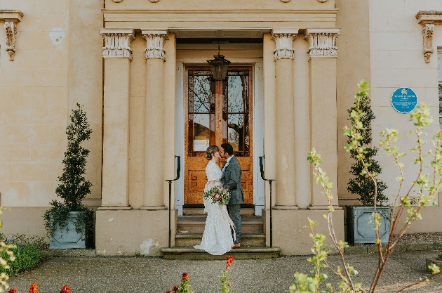 Bride and groom standing on the steps of Gaskell's House