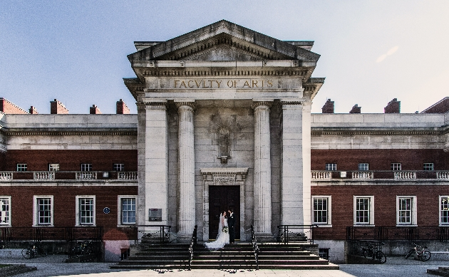 Bride and groom on the steps of the University of Manchester on a sunny day