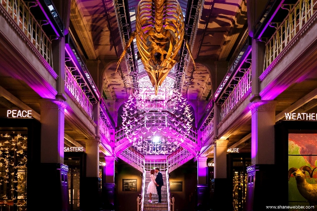 Inside the University of Manchester at night, bride and groom standing on the steps