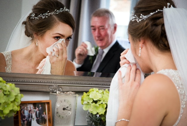Bride looking in the mirror and wiping a tear from her face as her father looks on