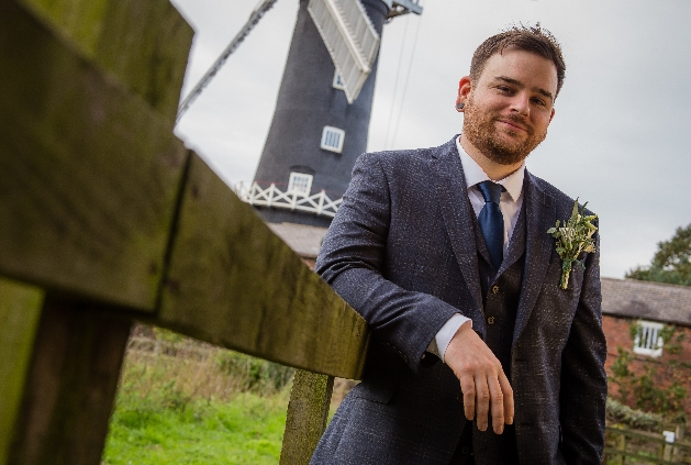 Grooms in his wedding attire leaning on a fence