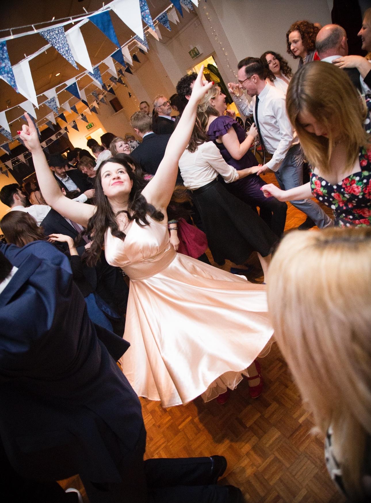 Bride in retro wedding dress dancing with her guests