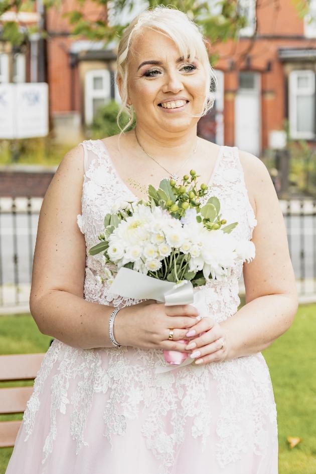 Bride in her wedding dress holding her wedding bouquet