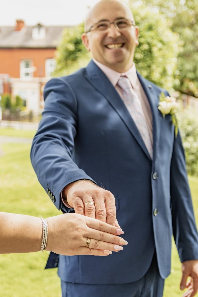 Groom in his big-day suit holding his bride's hand