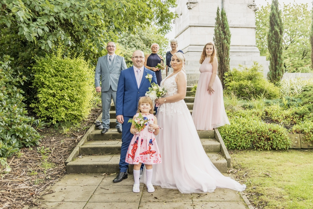 Bride and groom standing with their bridal party on the steps of their wedding venue