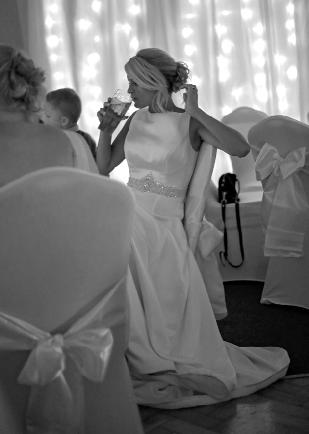 Shot of a bride in a chair drinking at her wedding reception