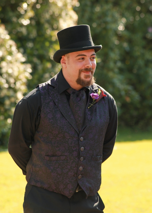 Groom in his wedding outfit showing off his top hat