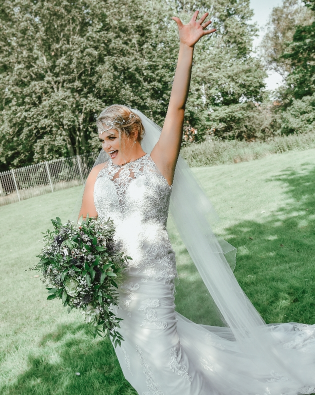 Happy bride holding her hand in the air with her wedding bouquet
