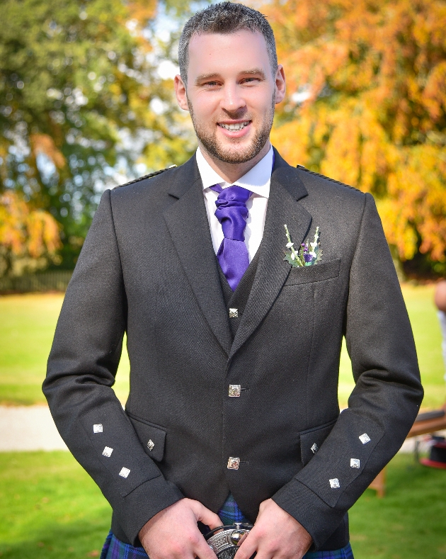 Smiling groom standing in his wedding attire which is a kilt