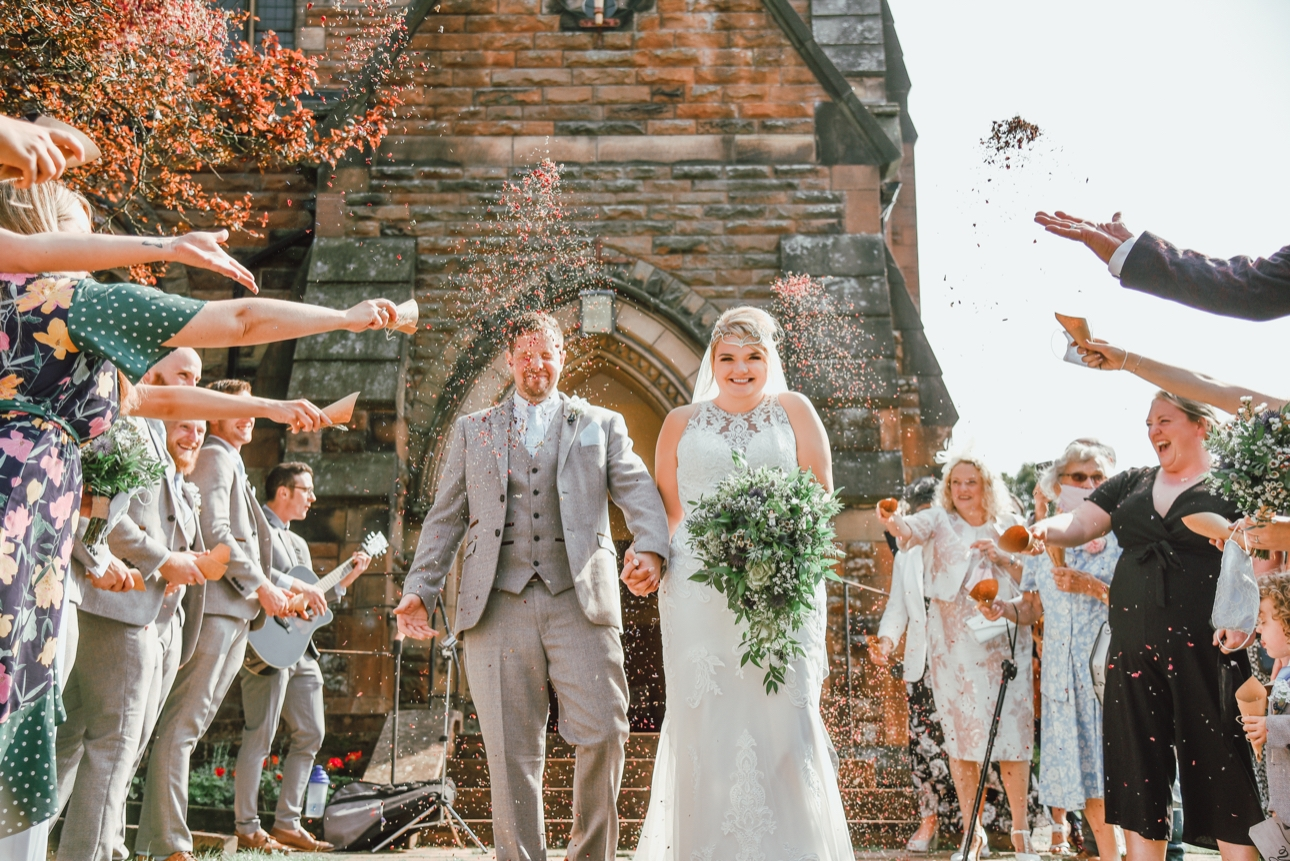 Bride and groom leaving church with confetti being thrown in their face