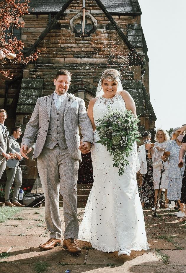 Beaming bride and groom leaving church