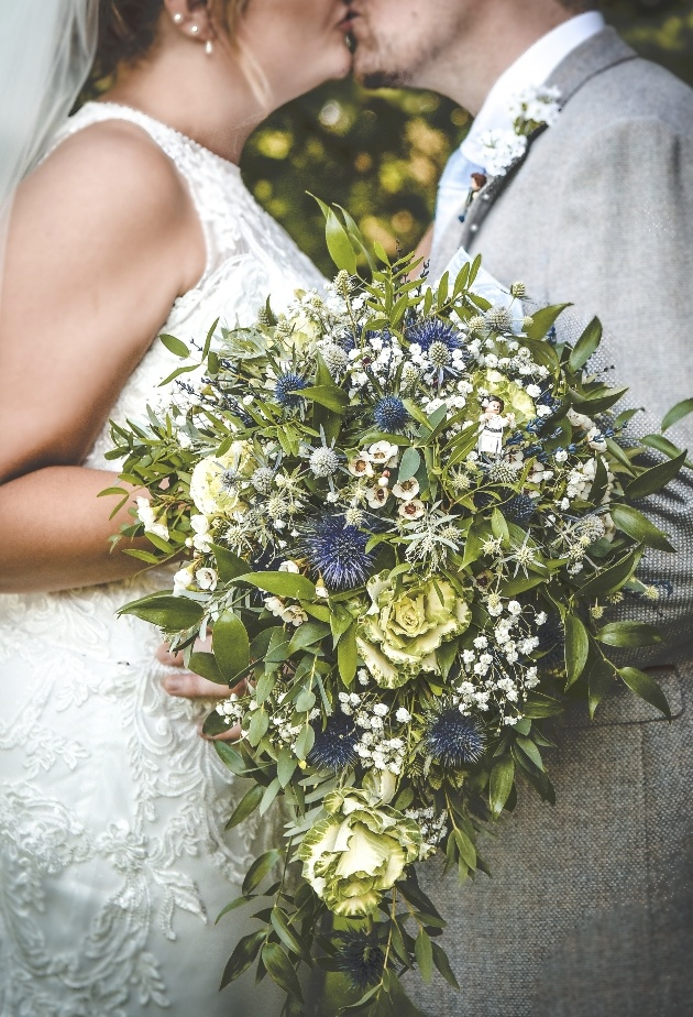 Bride's bouquet with couple kissing in background