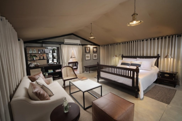 safari tent bedroom with bed, sofa, table, chairs and own bar